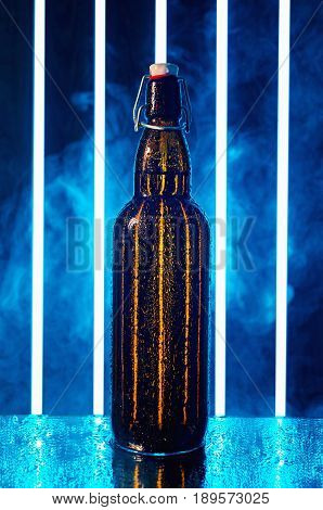 wet beer bottle with wood cork on a wet mirror in the smoke and bright light strips