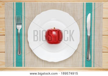 red apple on a white plate on the table with a knife and fork