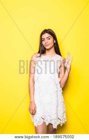 Happy Young Woman Showing Ok Sign With Fingers An Winking Isolated On A Yellow Background