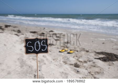 Wooden plaque with an inscription SOS on the background of the sea and sandy beach
