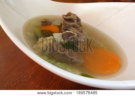 Beef soup with vegetables, Filipino favorite Beef bone soup with cabbage and onions served in a deep white bowl. It is a favorite dish in the Philippines.