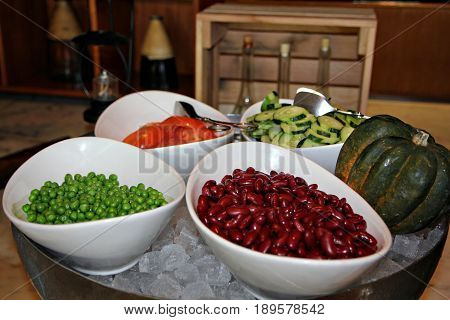 Bean salad bar Red beans, peas, tomatoes and sliced cucumber on top of ice cubes in salad bar