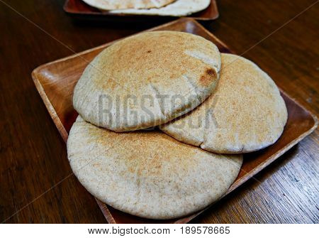 Freshly made naan bread  three pieces of Naan bread freshly made and served on a wooden platter