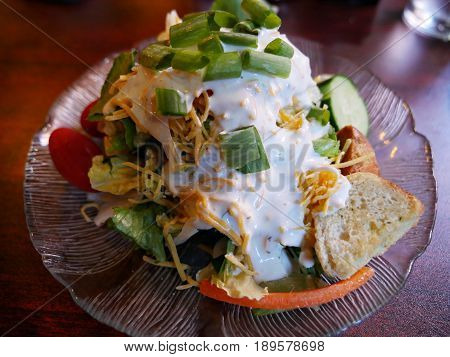 Caesar salad with a slice of garlic bread Fresh Caesar salad with cream and topped with onions, served in a round decorated clear plate