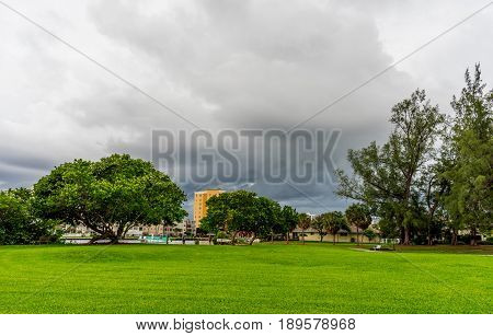 dark storm clouds approaching from the east as seen from a green field in a park on the intracostal waterway