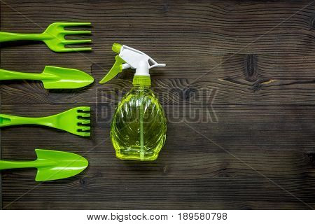 gardening equipment with spray, rake and trowel for growing green plants on wooden desk background top view mockup