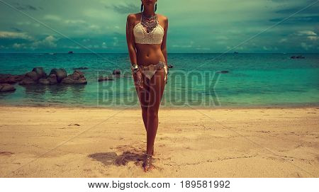 Slim and tanned girl in trendy Boho style on the beach. Girl in a white knit swimsuit with silver jewelry . Bracelets and rings with turquoise stones.