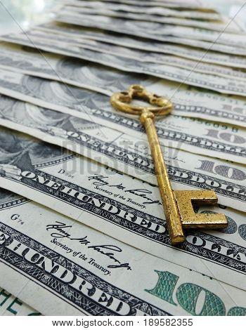 Gold key on assorted hundred dollar bills