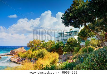 CRETE ISLAND GREECE JULY 01 2011: Classical Greece hotel villa on stone beach among green trees for tourists guests. Greek hotel architecture. Greece island holidays tours travel journey. Panorama