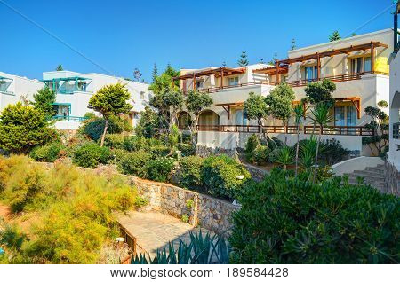 CRETE ISLAND, GREECE, SEP 08, 2012: Classical Greece hotel villa on stone beach among green trees for tourists guests. Luxury Greek hotel architecture. Greece island holidays tours travel. Panorama
