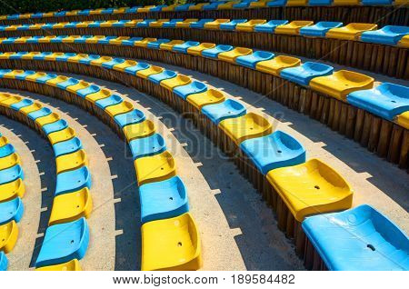 Perspective diagonal curve abstract view on amphitheater theater blue yellow plastic seats. Seats circle. Amphitheater seats architecture background. Diagonal curve. Abstract fractal color background