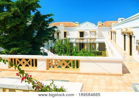 CRETE ISLAND, GREECE, JULY 01, 2011: View on hotel villas for tourists guests. Green tropical palm trees, white houses villas. Classic hotel architecture. Famous Greece islands holidays tours