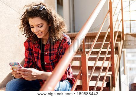 Portrait of joyful mulatto girl typing message on smartphone. She is sitting on steps and smiling