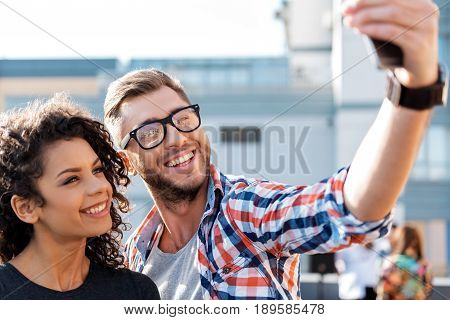 Happy loving couple is making selfie on smartphone. They are standing outdoors and laughing. Portrait