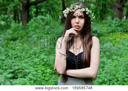 Portrait Of An Emotional Young Girl With A Floral Wreath On Her Head And Shiny Ornaments On Her Fore