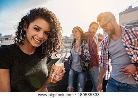 Cheers. Portrait of excited mulatto girl drinking beer while looking at camera with happiness. Her friends are dancing and laughing on background
