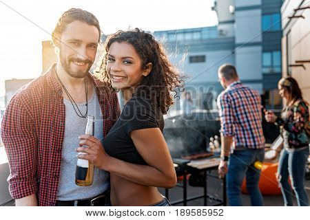 Happy loving couple is having fun on party on roof. They are embracing and smiling. Their friends are frying meat on background