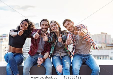 Everything is okay. Excited young people are giving thumbs up and smiling. They are sitting on roof border and relaxing. Portrait