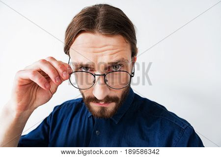 Clever young man is touching his glasses and staring at camera with seriousness. He is standing isolated on background. Waist up portrait