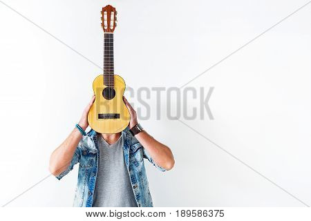 Music is my life. Young man is covering his face by small guitar and standing. Isolated and copy space in right side