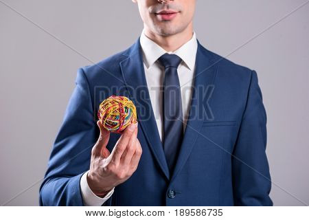 Calm businessman keeping rubber sphere in hand. Inspiration concept. Copy space