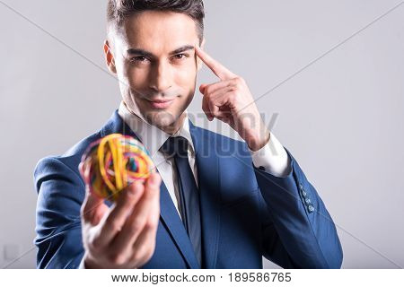 Portrait of outgoing man thinking about creative idea while keeping rubber sphere in arm. He looking at camera. Concentration concept