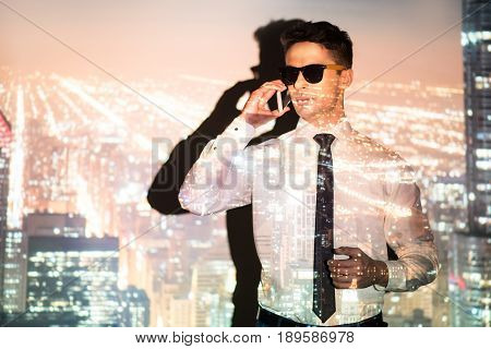 Double exposure of male expressing seriousness while speaking by mobile in modern metropolis projection
