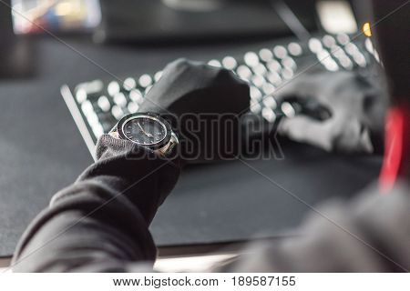 Close up arm of computer burglar watching at clock. He typing on keyboard while downloading information from digital device