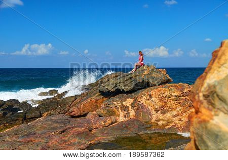 Beautiful young girl seats on big stone rock on rock stone beach on Grete Island Greece. Island rocks beach. Woman in red. Greece islands holidays vacations tours famous sightseeing destinations