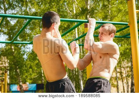Fitness man at the bar. Exercising outdoors in the Park. Street workout