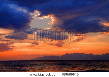 Beautiful mysterious dramatic romantic colorful red orange blue sun dusk sunset on Ionian Sea on island sand beach. Twilight glow. Greece islands holidays vacation tours trip travel