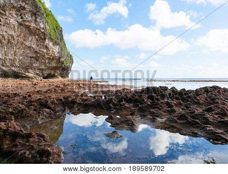 Niue, South Pacific - May 25, 2017;  Mother and son exploring rock pools in distance on coral shelf on tropical Niue