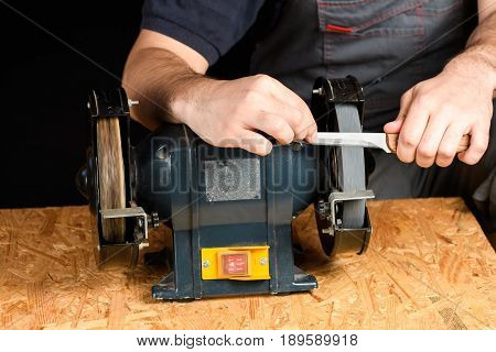 A Man In Working Clothes Hones Professional Sharpening Kitchen Knive