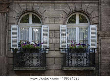 Two windows with shutters and wrought iron window boxes or balconies in a brick building in Toulouse, France.