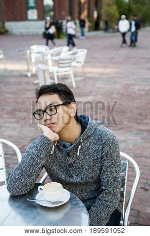 Young asian man in outdoor cafe with cup of coffee looking away being bored and unhappy