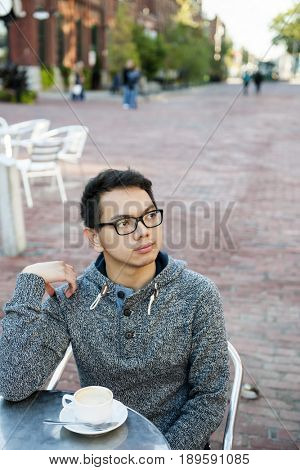 Young asian man in outdoor cafe with cup of coffee looking away serious and contemplative