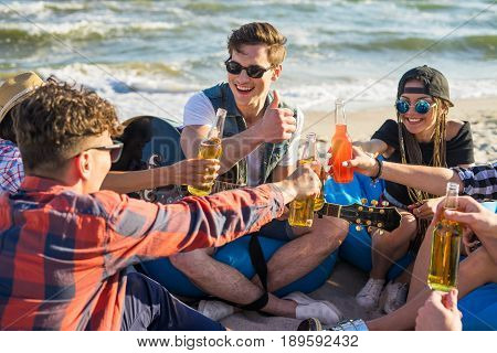 cheers. group of friends on the beach party drinking alcohol and clink glasses . Happy youth time. One guy is showing thumbs up.