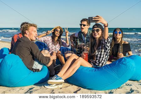 cheerful group of friends shooting selfie and having fun at the beach. They play guitar and drink alcohol. Happy youth time