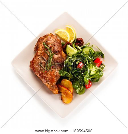 Grilled beefsteak with vegetables on white background