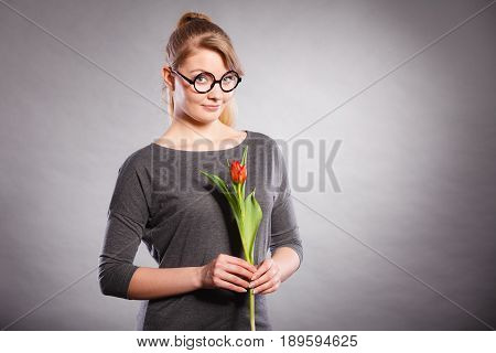 Leisure feelings flora nature beauty feminine concept. Seducive nerdy girl holding tulip. Young blonde lady with red flower.