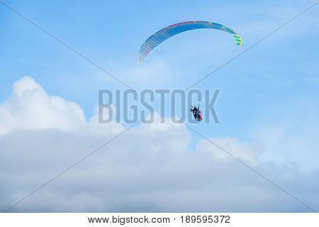 Paragliders in bright blue sky, tandem of instructor and beginner.