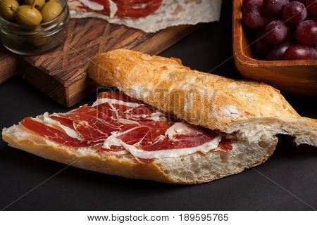 Jamon Iberico with white bread, olives on toothpicks and fruit on a dark background.