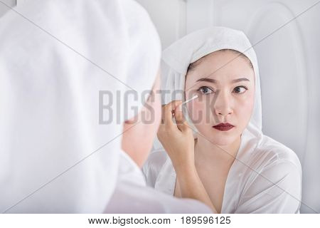 Woman Looking Mirror And Remove Makeup Beside Eye With A Cotton Swab