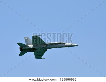 Modern navy fighter jet against blue sky side view