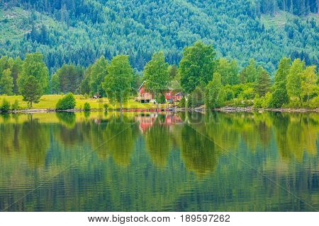Norwegian Country Houses In Mountains On Lake Shore
