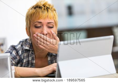 Bored Young Woman Yawning As She Works On A Tablet