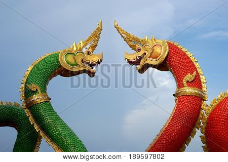 red and green serpent statue with beautiful sky background