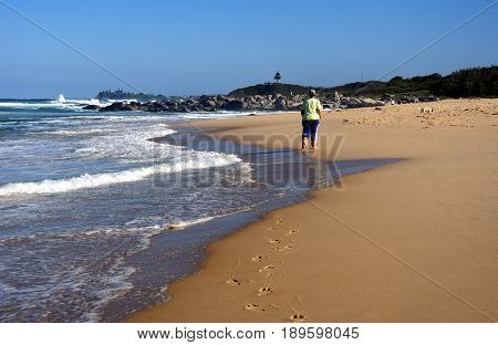 Beach at Tuross Head. Tuross Head is a seaside village on the south coast of New South Wales Australia. Lady is wearing yellow t-shirt with blue pants and walking on the beach.