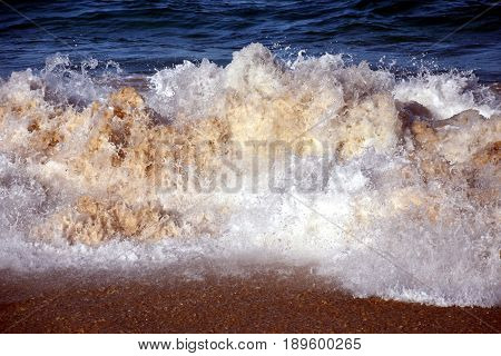 Water foam of the waves crushing into the shore texture. Wild powerful waves are splashing and forming foam.