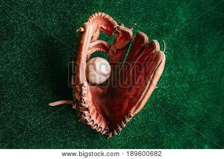 Old leather glove of the baseball catcher and the ball